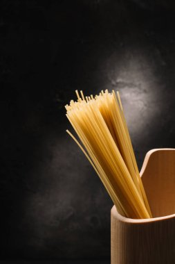 bunch of raw spaghetti in wooden container with garlic on black surface