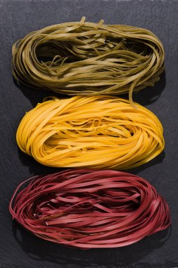 top view of various colored spaghetti nests on black