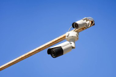 close up view of security cameras on pole against bright blue sky
