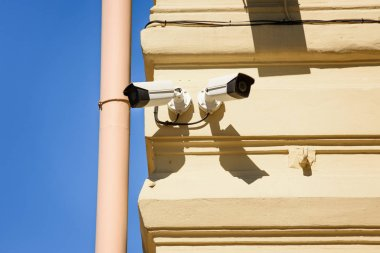 close up view of security cameras on yellow building facade