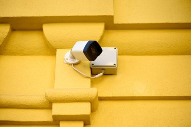 Close up view of security camera on yellow building facade stock vector