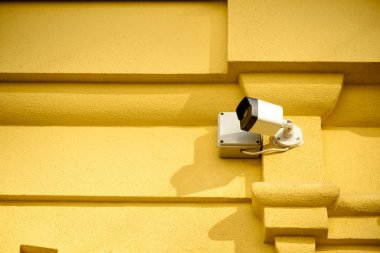 close up view of security camera on yellow building facade