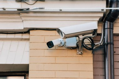 close up view of security cameras on orange colored building facade