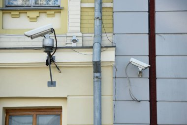 close up view of security cameras on different buildings facades