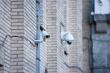 close up view of security cameras on brick building facade