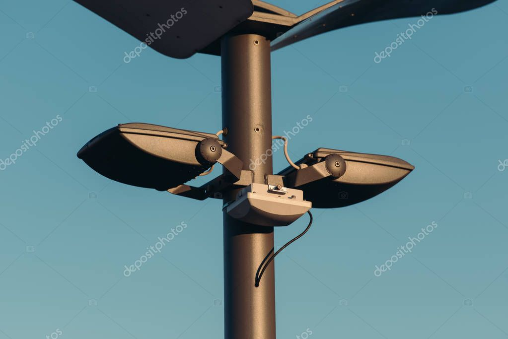 close up view of street lights on pole with blue sky on background