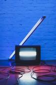 tónusú kép rendezett retro tv-készülék, a kábelek és a lámpa téglafal háttér