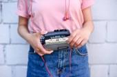 Fényképek vágott lövés a nő a gazdaság retro magnó kezek ellen fehér téglafal fülhallgató