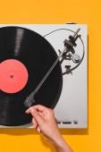 oříznuté záběr ženy zapnutí přehrávače vinyl izolované na žluté