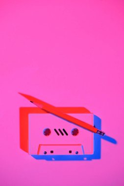 Toned pink picture of retro audio cassette and pencil on tabletop stock vector