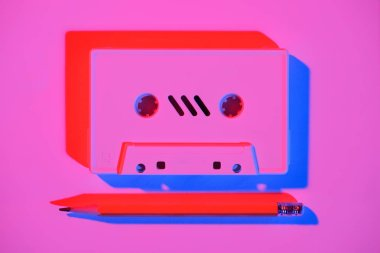 toned pink picture of retro audio cassette and pencil on tabletop