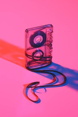 close up view of retro audio cassette and tape on pink backdrop