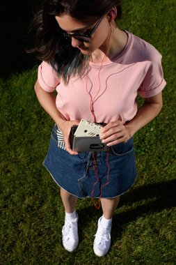 high angle view of stylish young woman in sunglasses and earphones with retro audio cassette and player in hands standing on green grass