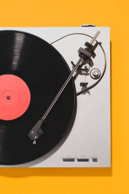 top view of retro vinyl player and record isolated on yellow
