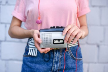 cropped shot of woman with earphones holding retro cassette player in hands against white brick wall