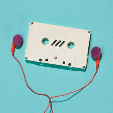 flat lay with white retro audio cassette and earphones isolated on blue