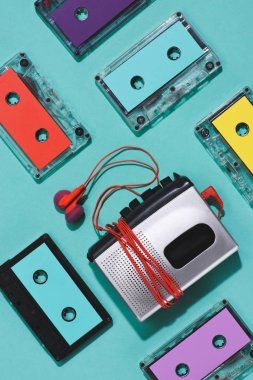 flat lay with colorful retro audio cassettes, cassette player and earphones isolated on blue