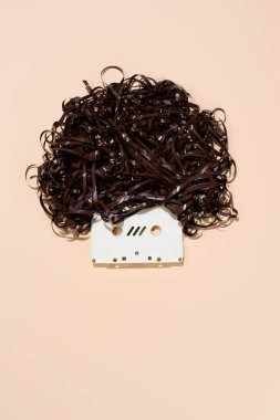top view of retro audio cassette with tape isolated on beige