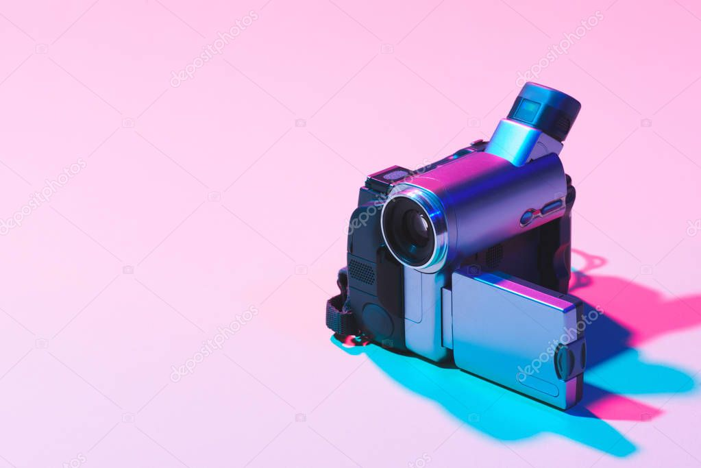 close up view of digital video camera on pink background