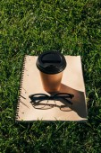 Photo close up view of coffee to go, notebook and eyeglasses on green grass