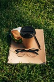close up view of notebook, sandwich, eyeglasses and coffee to go on green grass