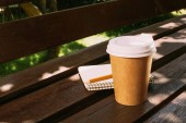 Fotografie close up view of notebook with pencil and disposable cup of coffee on wooden bench