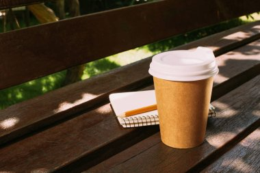 close up view of notebook with pencil and disposable cup of coffee on wooden bench