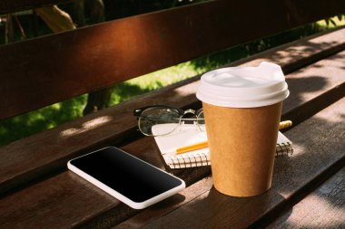 close up view of smartphone, notebook, eyeglasses and coffee to go on wooden bench
