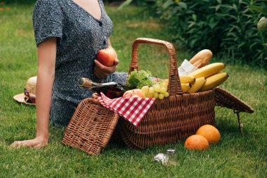 cropped image of woman sitting on green grass at picnic and holding ripe apple