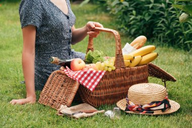 cropped image of woman sitting on green grass at picnic and touching basket with food