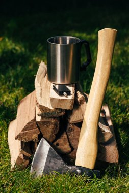cup on pile of firewood on green grass in park
