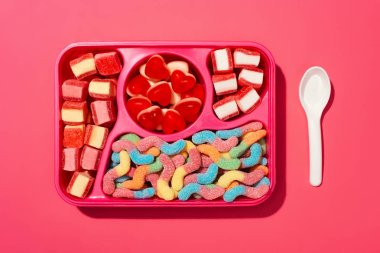 top view of gummy candies on plastic tray on pink surface