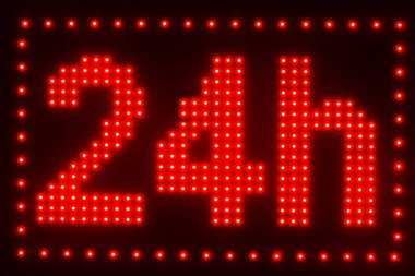 close up view of illuminated twenty four hour sign on dark background