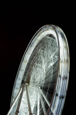 selective focus of blurred observation wheel at night on black background