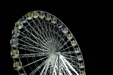 Selective focus of illuminated observation wheel at night on black background stock vector