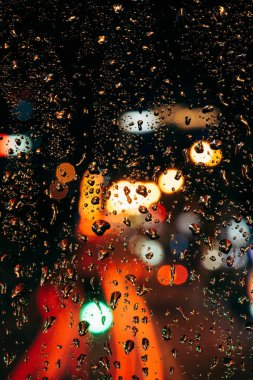 Close up view of raindrops on window and bokeh city lights on background