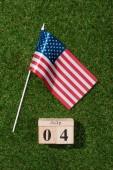 horní pohled na americký stožáru a dřevěné kalendáře s 4.července datum na zelené trávě, koncept den nezávislosti Ameriky