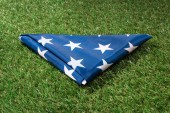 close up view of folded american flag on green lawn, americas independence day concept