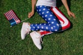 Fotografie partial view of woman with flagpole in leggins with american flag pattern resting on green lawn, americas independence day holiday concept