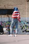 zadní pohled na ženu s americkou vlajkou v ruce stojí na ulici, 4. července dovolená concept