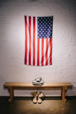 Close up view of american flag hanging on white brick wall and arranged military uniform on wooden bench stock vector