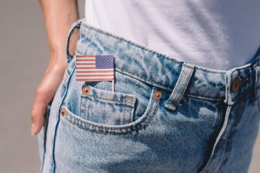 partial view of woman in jeans with american flagpole in pocket, americas independence day holiday concept