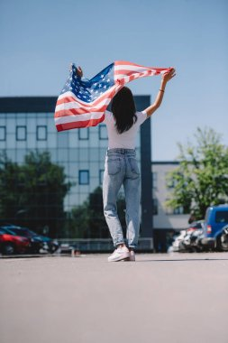 back view of woman with american flag in hands standing on street, 4th july holiday concept