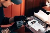 Selektivní fokus tatér v rukavice s tetování stroj v salonu