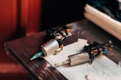 close up view of tattoo machines on wooden tabletop at tattoo salon