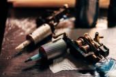 zblízka pohled tetovací strojky na dřevěnou desku na tattoo salon