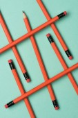 Fotografie elevated view of arranged red graphite pencils with erasers on green