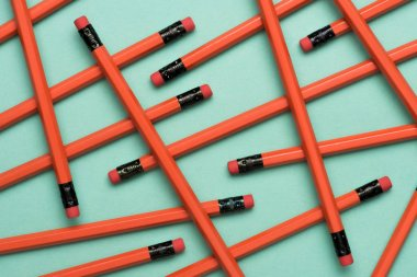 top view of arranged red graphite pencils with erasers on green