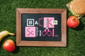 flat lay with fresh apples, banana, burger and blackboard with back to school lettering made of pink and white objects on green lawn
