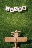 Fotografie top view of wooden toy plane and learn inscription made of blocks on green grass